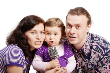 Mother, daughter and father sing into the microphone.