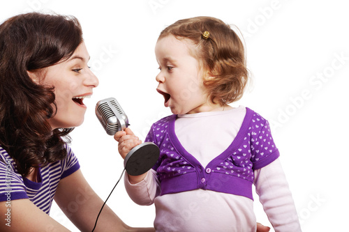 Mother and her little daughter sing into the microphone
