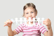little girl holding garland of paper little people isolated