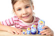 little girl playing with blue matryoshka and smiling