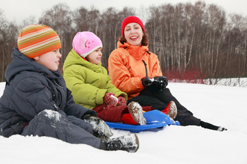 young mother, little son and daughter sitting on snow