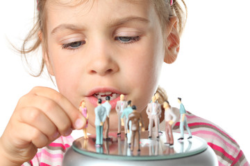 little girl plays with small toy figures of people isolated