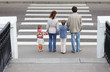 parents holds hand of  daughter and son and standing near road