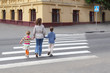 young mother holds hand of little daughter and son and crossing