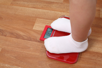 Girl stands on the weights. feet in white socks on scales