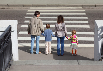 parents holds hand of daughter and son and standing on crossing