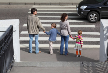 mother and father holds hand of children and standing in city