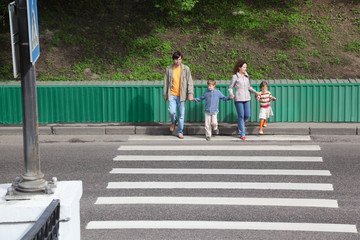 parents holds hand of little daughter and son and crossing