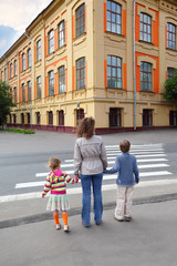 mother holds hand of little daughter and son and crossing