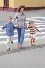 mother holds hand of little daughter and son in city