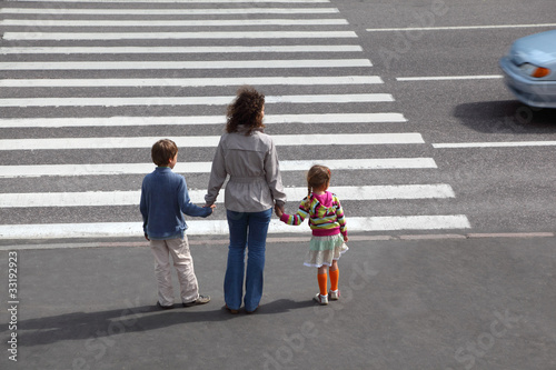 mother holds hand of daughter and son and is going on road