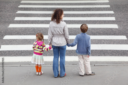 mother holds hand of daughter and son and standing near road