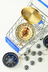 golden compass in cart and ten black compasses isolated