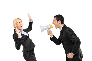 Angry businessman yelling via megaphone to a scared businesswoma