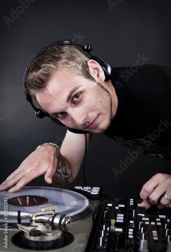 discjockey mit kopfhörern regelt mischpult