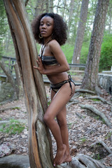 Pretty black woman in bathing suit outside by a tree
