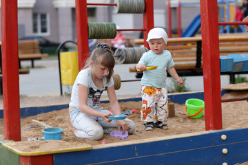 Siblings play in sandbox
