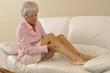 Seniorin massiert ihre Beine