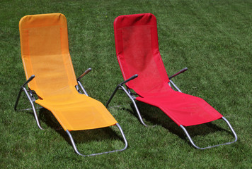 Red and yellow sunbed on grass outdoor