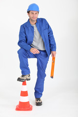 Builder with foot on traffic cone.