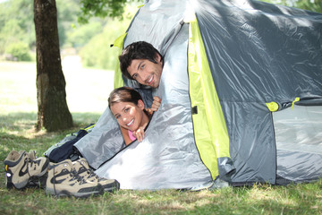 Young couple peeking out of their tent