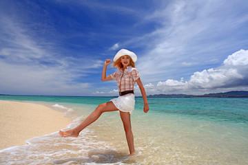波打ち際を歩く笑顔の女性