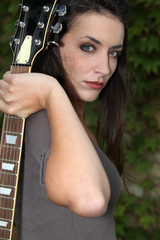 dark hair woman holding a guitar looked mysterious