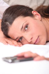 Closeup of a woman in bed reaching for her cellphone