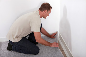 Man installing carpet in room