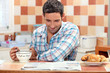 Smiling man having continental breakfast in his kitchen