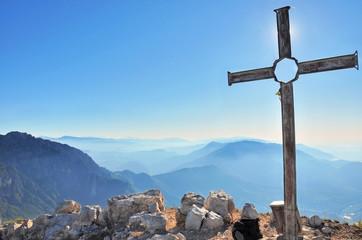 croix devant le soleil au sommet d'une montagne