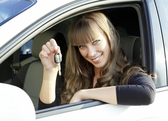 Cheerful young lady sitting in a car and showing key