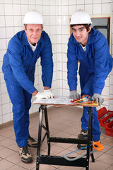 two skilled tradesman in blue jumpsuites watching a drawing