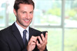 Businessman texting on a mobile phone
