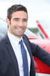 Smiling businessman standing next to a light aircraft
