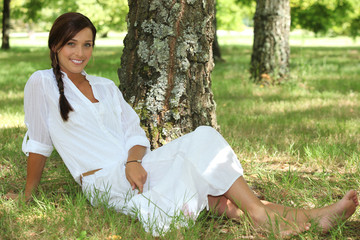 Woman dressed in white sat by tree