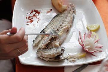 Woman eats dorado fish