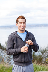 Mixed race man holding water bottle