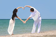 young couple making heart by arms on beach
