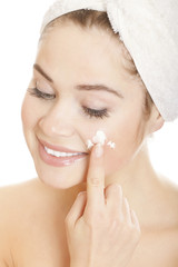 Beautiful smiling woman applying moisturizer cream on her face