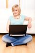junge Frau sitzt mit Laptop vor einem Sofa