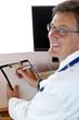 Älterer lächelnder Arzt am Schreibtisch schreibt Bericht