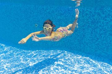 Happy smiling underwater kid in swimming pool