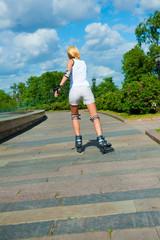 Blonde girl on roller skates rides