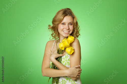 Attractive girl hugging a bouquet of yellow tulips