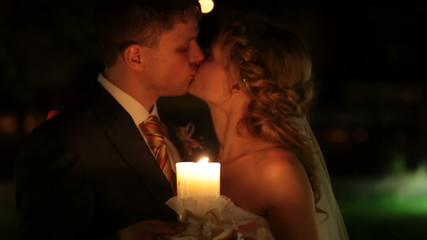 just married couple kissing by candlelight