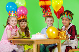 Girls and boy in party hats and crowns