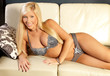sexy blond woman lying on couch in lingerie