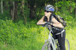 young biker woman getting rest in forest area