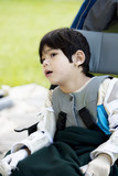 Four year old boy disabled with cerebral palsy sitting outdoors